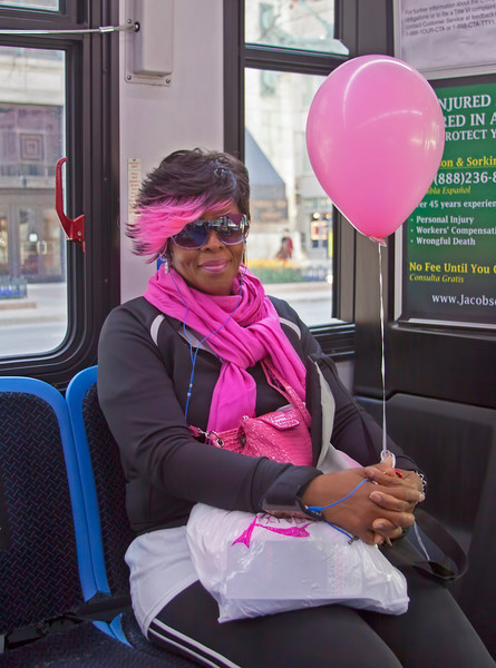 "Another shot from my trip to  Chicago last spring. This lovely lady had just participated in some sort of cancer awareness walk/run event. My friend and I caught a bus because my legs were wearing out on me, and we had the pleasure of sharing it with this lady. Being a photographer, I love color; the more the better and as they say ""if you've got it, flaunt it."" 2.20.12"