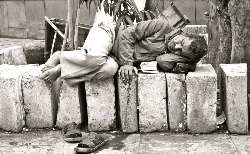 """Bed of Rocks""<br /> <br /> I saw this gentleman having a sound sleep on a rocky surface on a noisy heavy traffic street. Who needs a nice bed for a  power nap?<br /> <br /> <br /> The only society I like is rough and tough, and the tougher the better. There's where you get down to bedrock and meet human people. ~Robert W. Service ~"