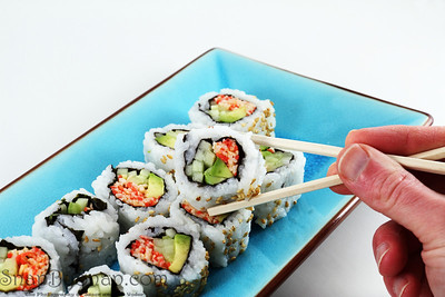 A hand holding a piece of sushi in a pair of chopsticks with more sushi in the background.