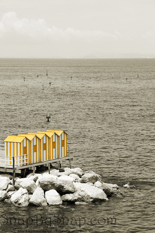 A selective color image of some yellow bath houses on the coast of Sorrento Italy.