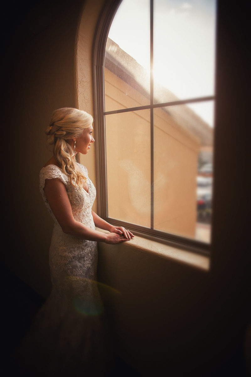 bride looing out of an arched windon on her wedding day