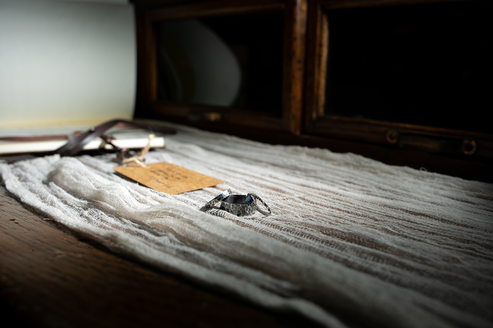 bride and groom's wedding rings witting on worn fabric next to a leather book