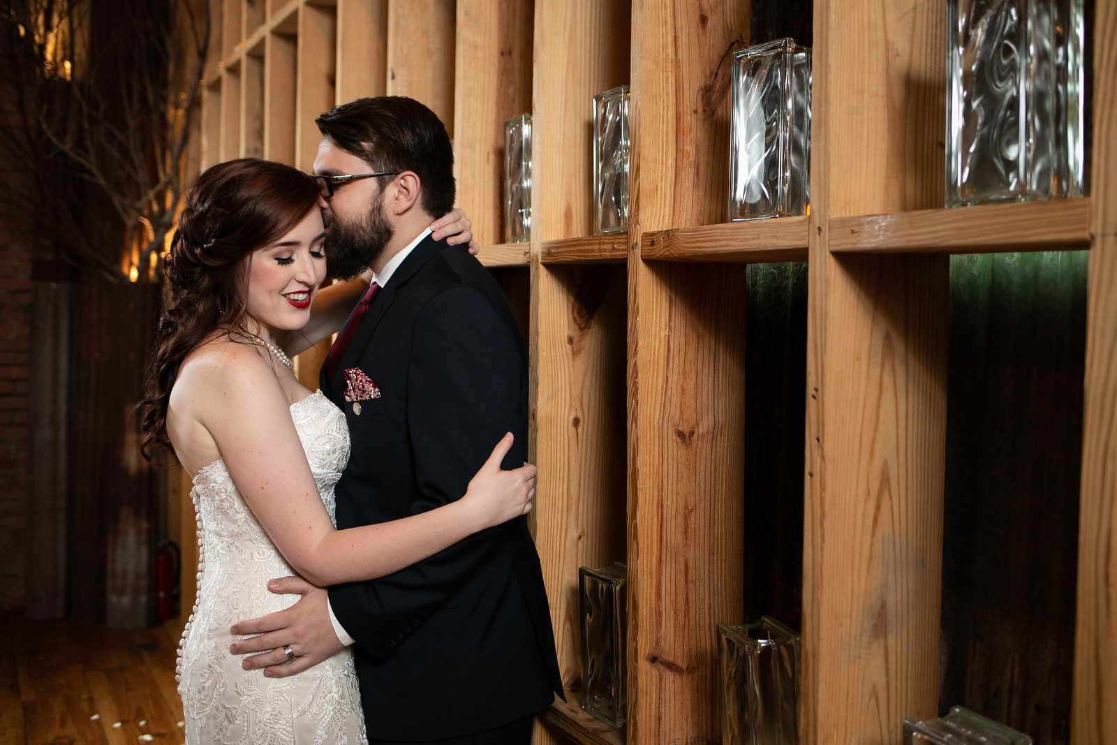 newlywed couple holding each other next to a wall buildt from reclaimed rafters