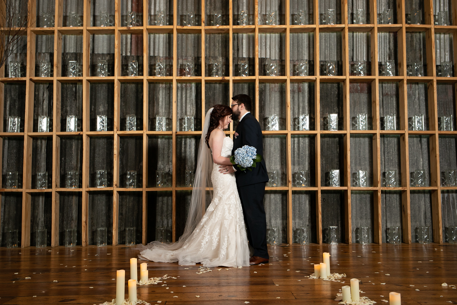 groom kissing bride on the head standing next to a giant bookcase wall filled with glass jars surrounded by flower petals and candles
