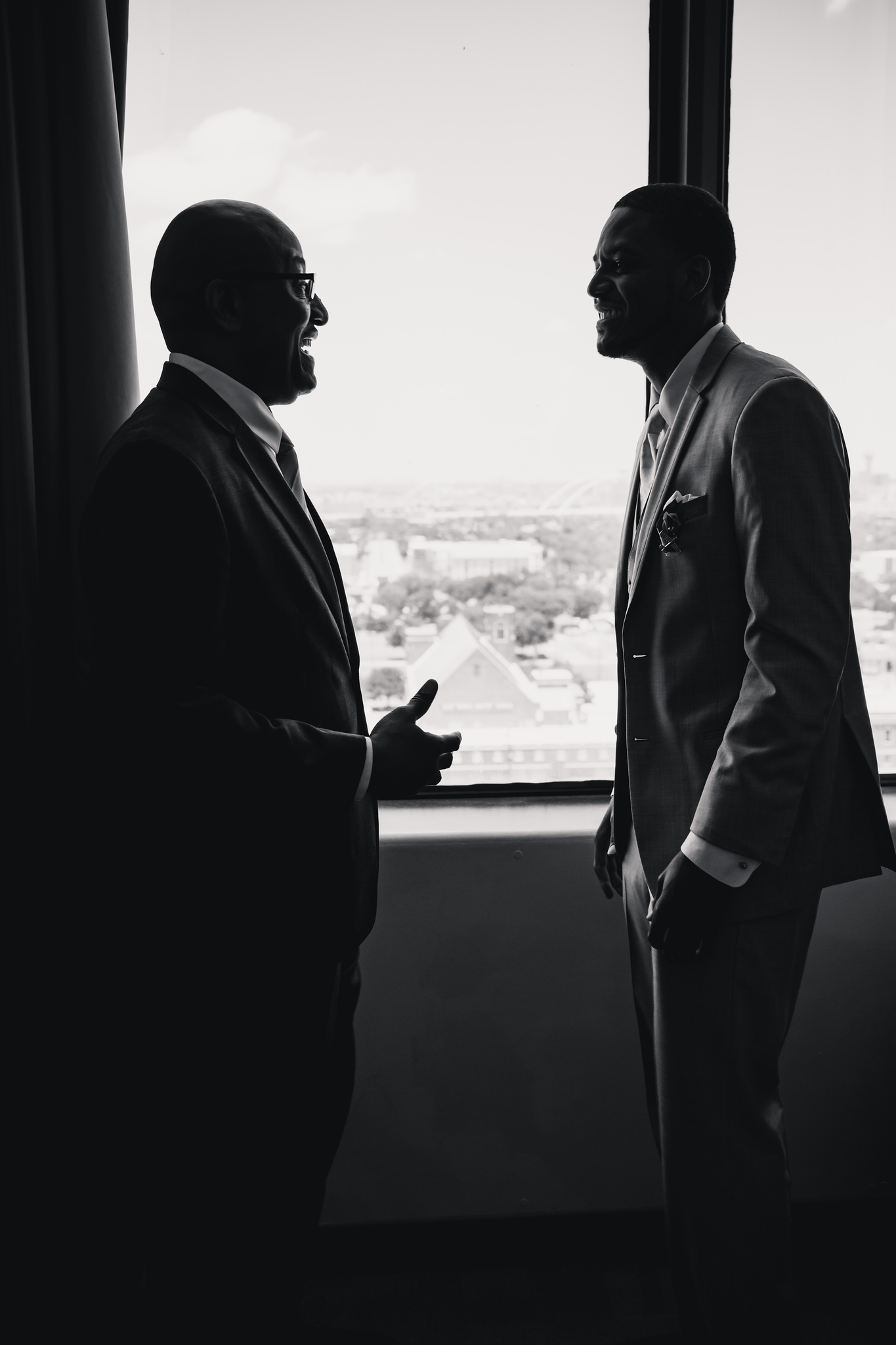 father and son talking while looking out a window overlooking Dallas south of Downtown
