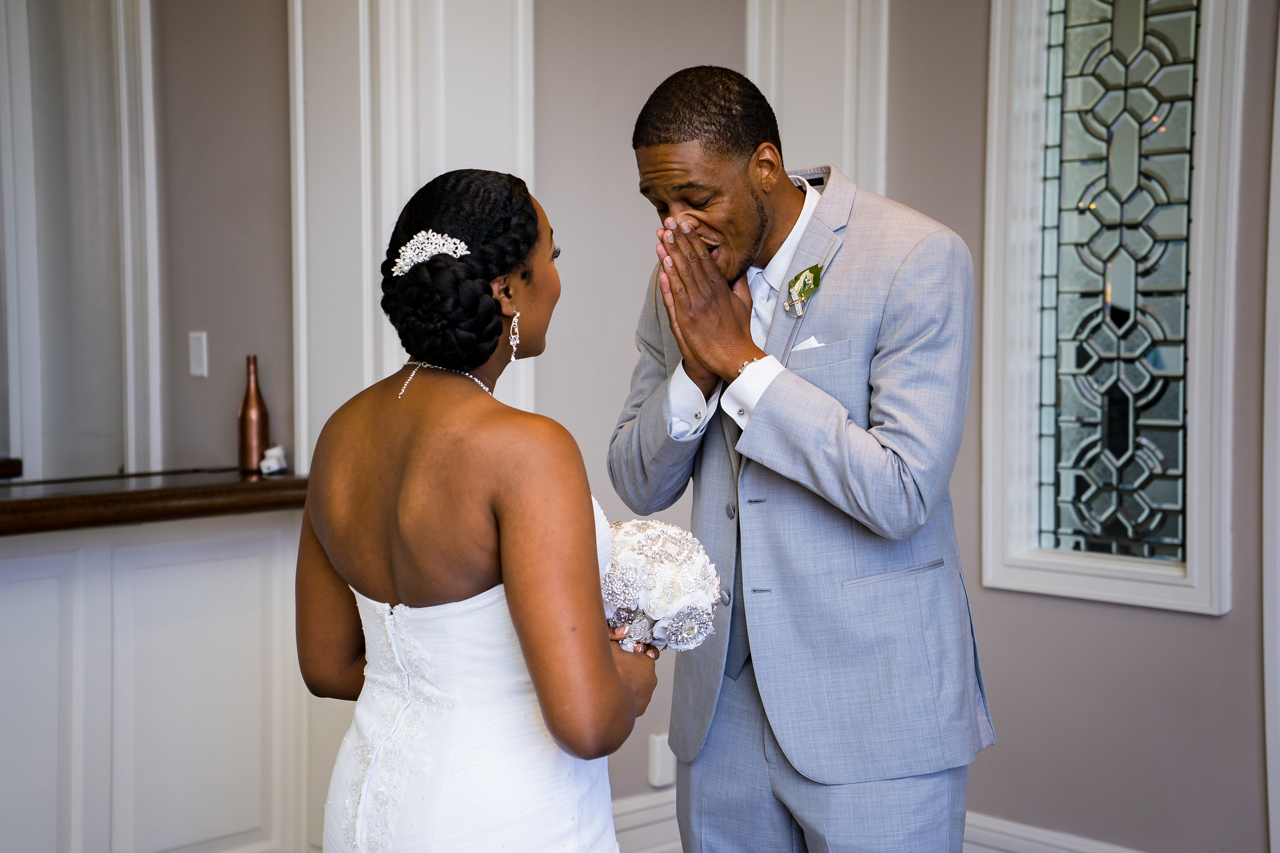 Groom wearing a sharkskin grey suit looking stunned as he sees his bride in her wedding dress for the first time