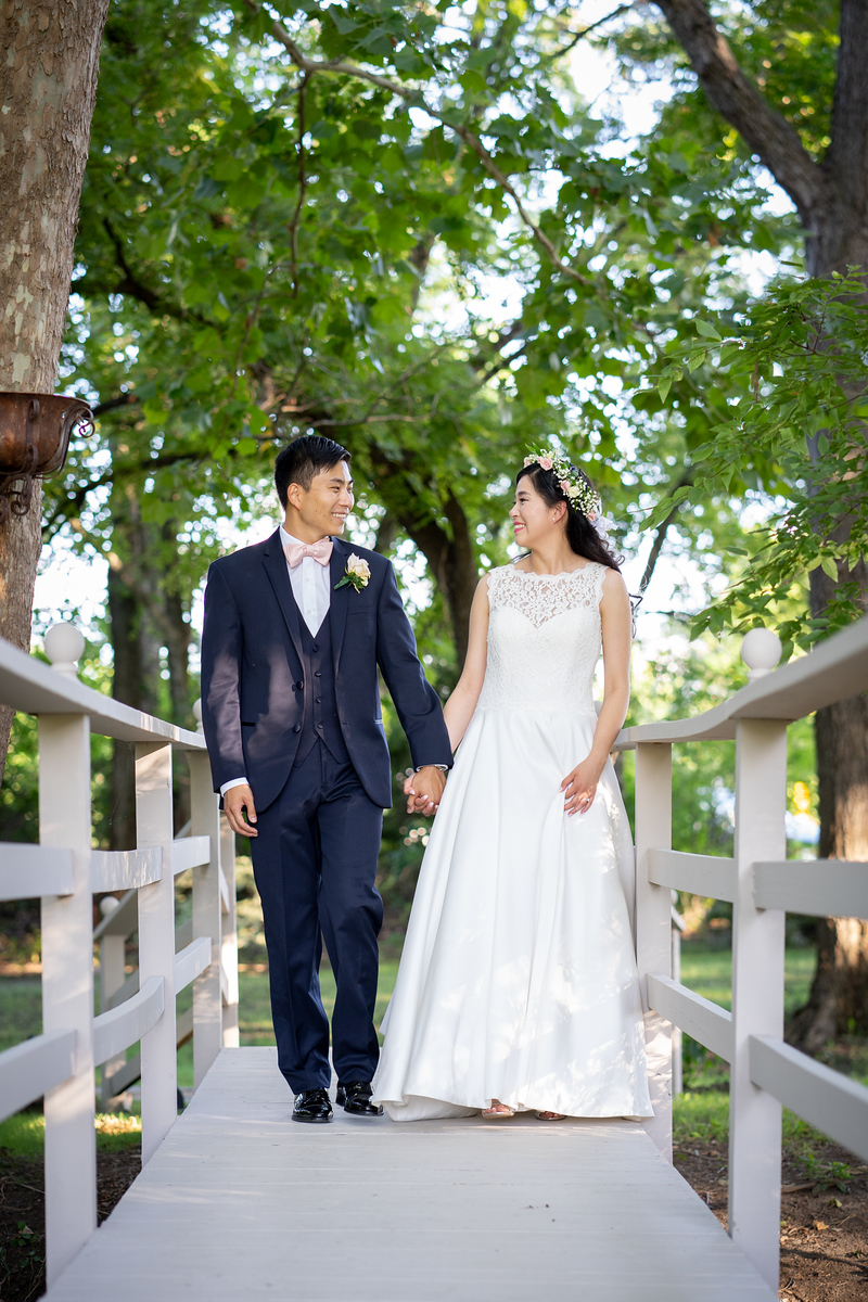 bride and groom walking across a white fence in a garden before their wedding