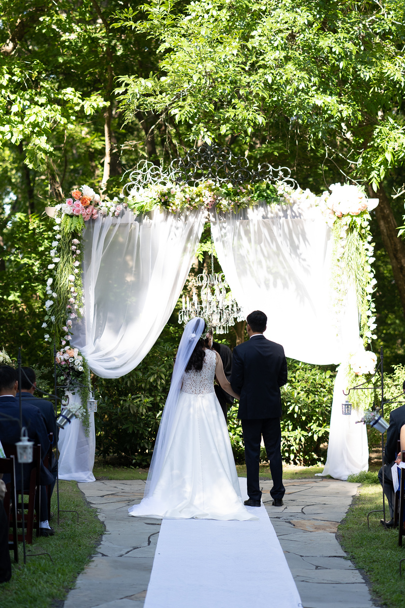 Outdoor ceremony area of River Road Chateau covered in white shear fabric and white runner down the aisle