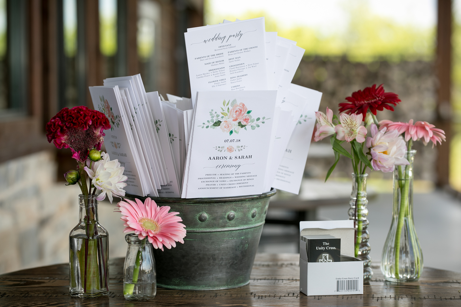 wedding programs in a galvanized bucket with rustic flower vases on a wooden table outside