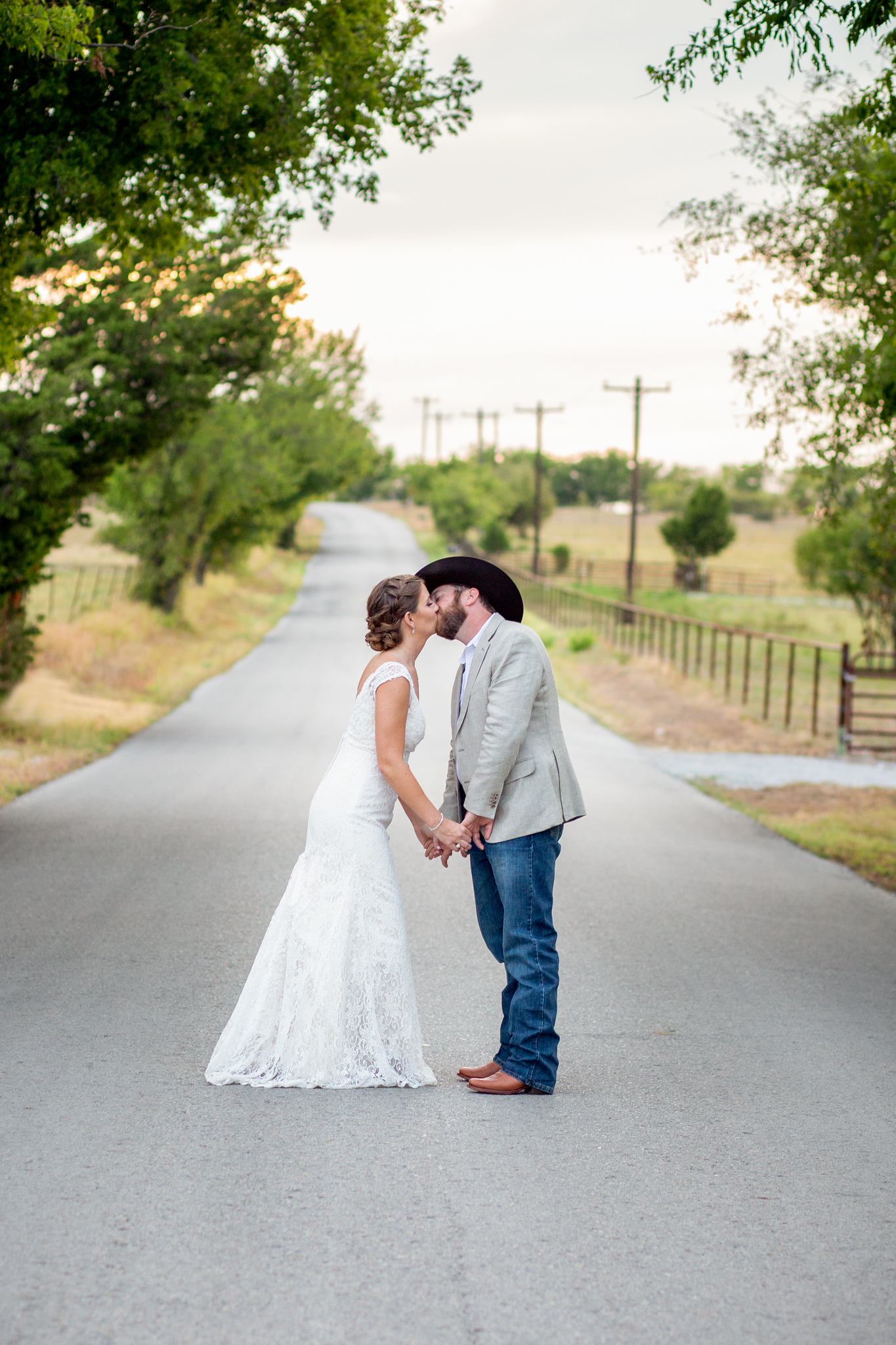 wedding couple kissing in the middle of a country road