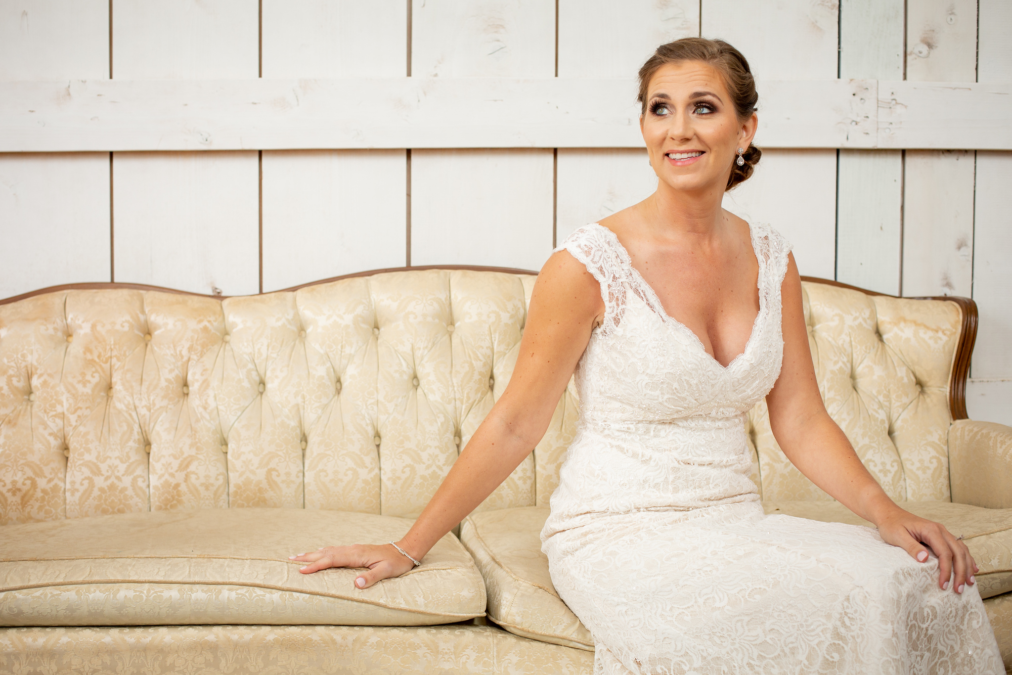 bride sitting on a classic antique cream-colored couch in front of rustic white wood wall