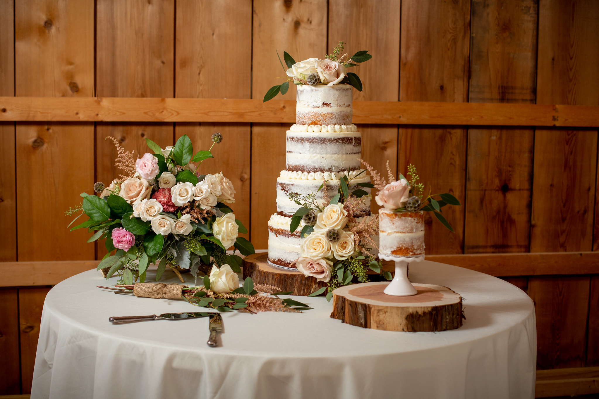 wedding cake on log platforms with natural flower bouquets