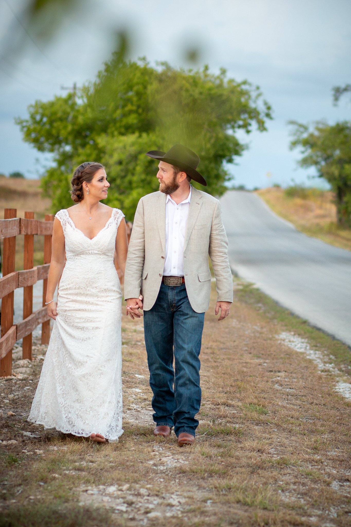 wedding couple holding hands while walking down a remote road