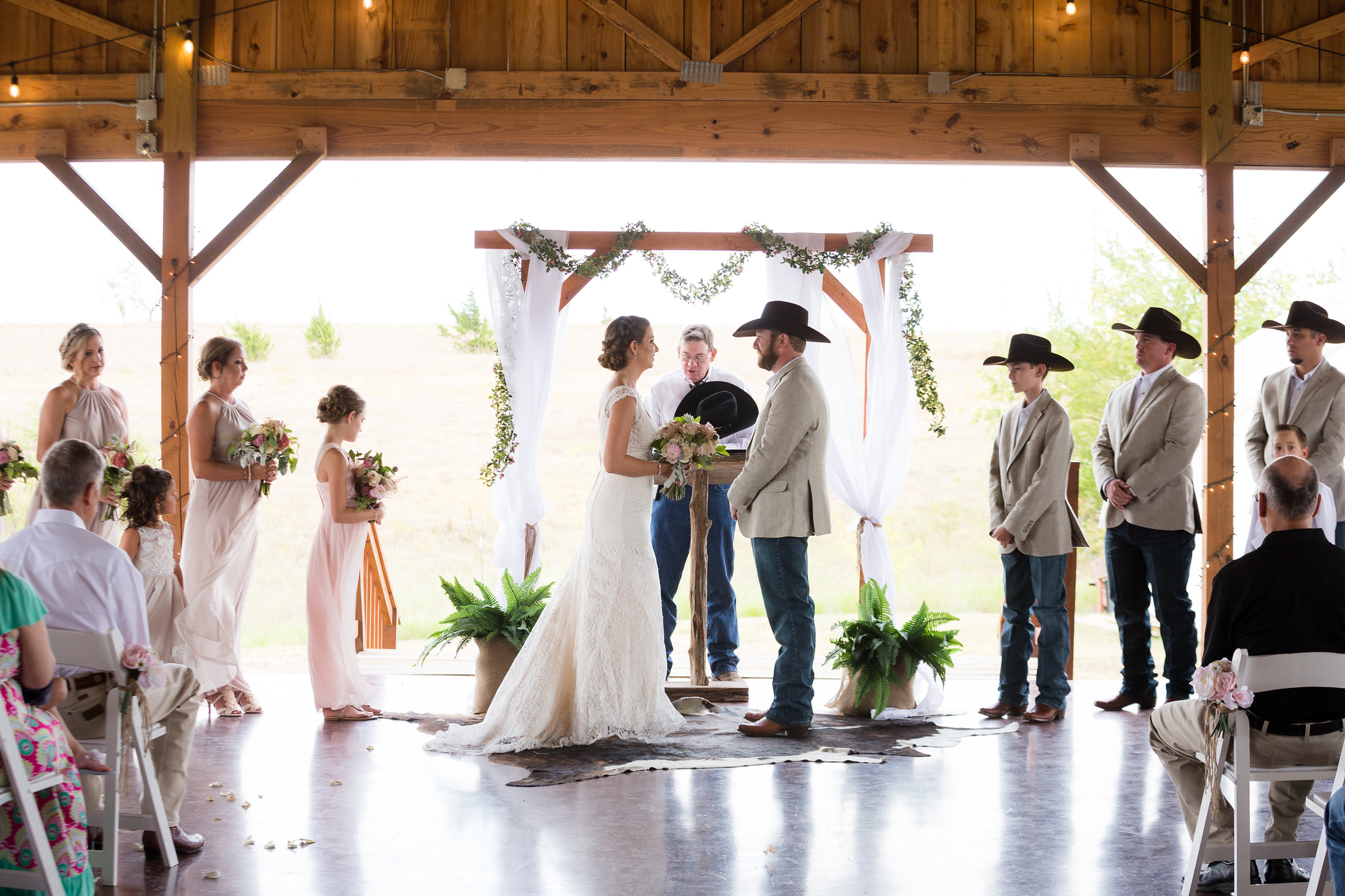 country wedding party with cowboy boots and hats standing at the altar