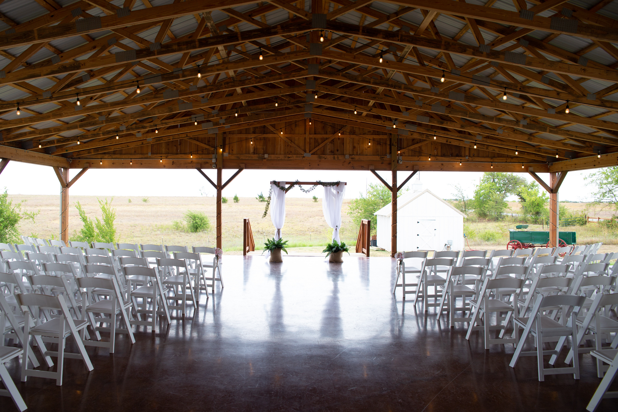 shaded outdoor wedding venue with white chairs string lights and a simple wedding arch