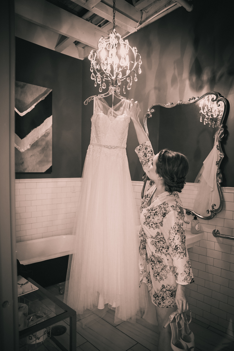 bride reaching for her wedding gown hanging from a chandelier at Brik
