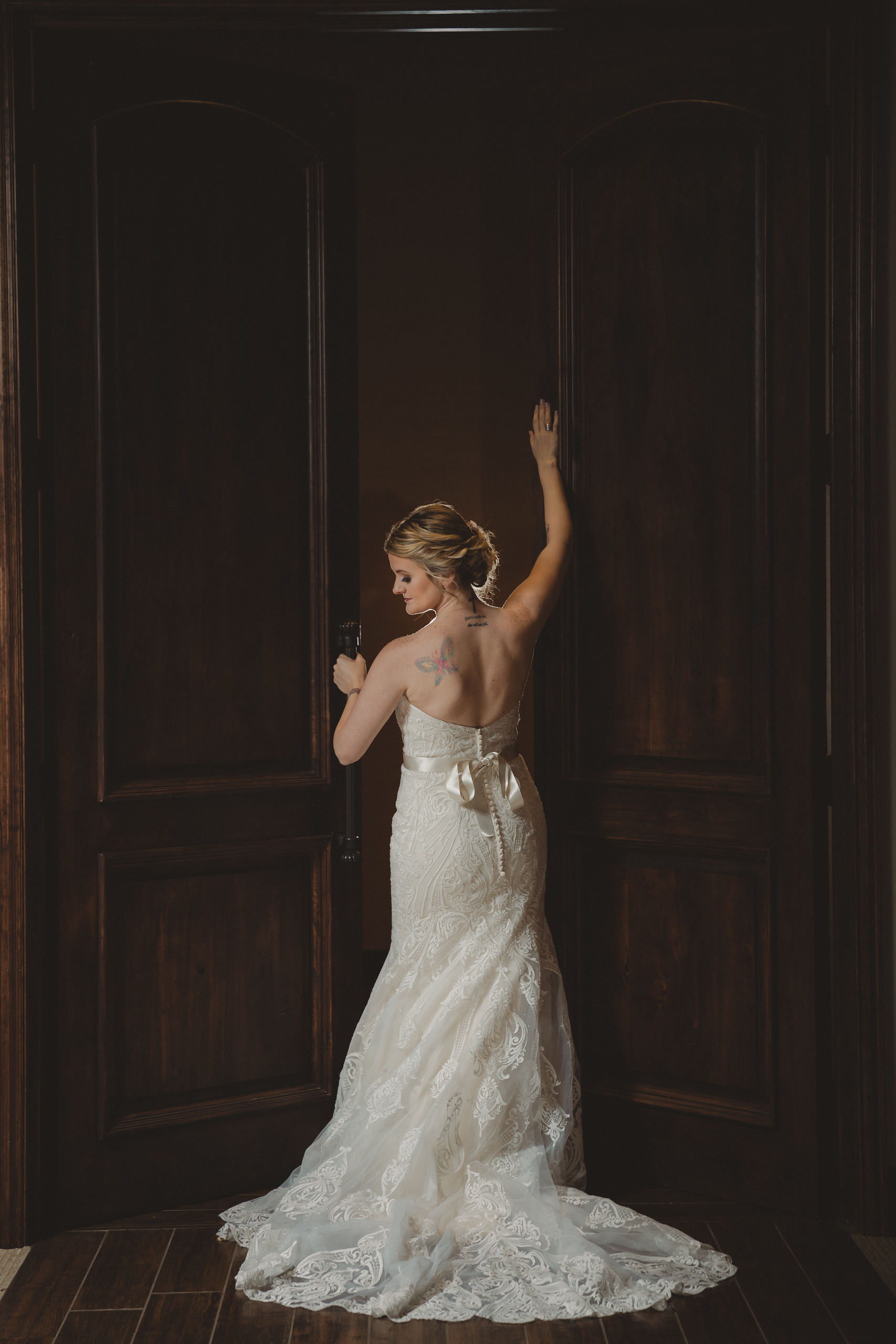 bride showing off the back of her lace wedding dress with a silk bow