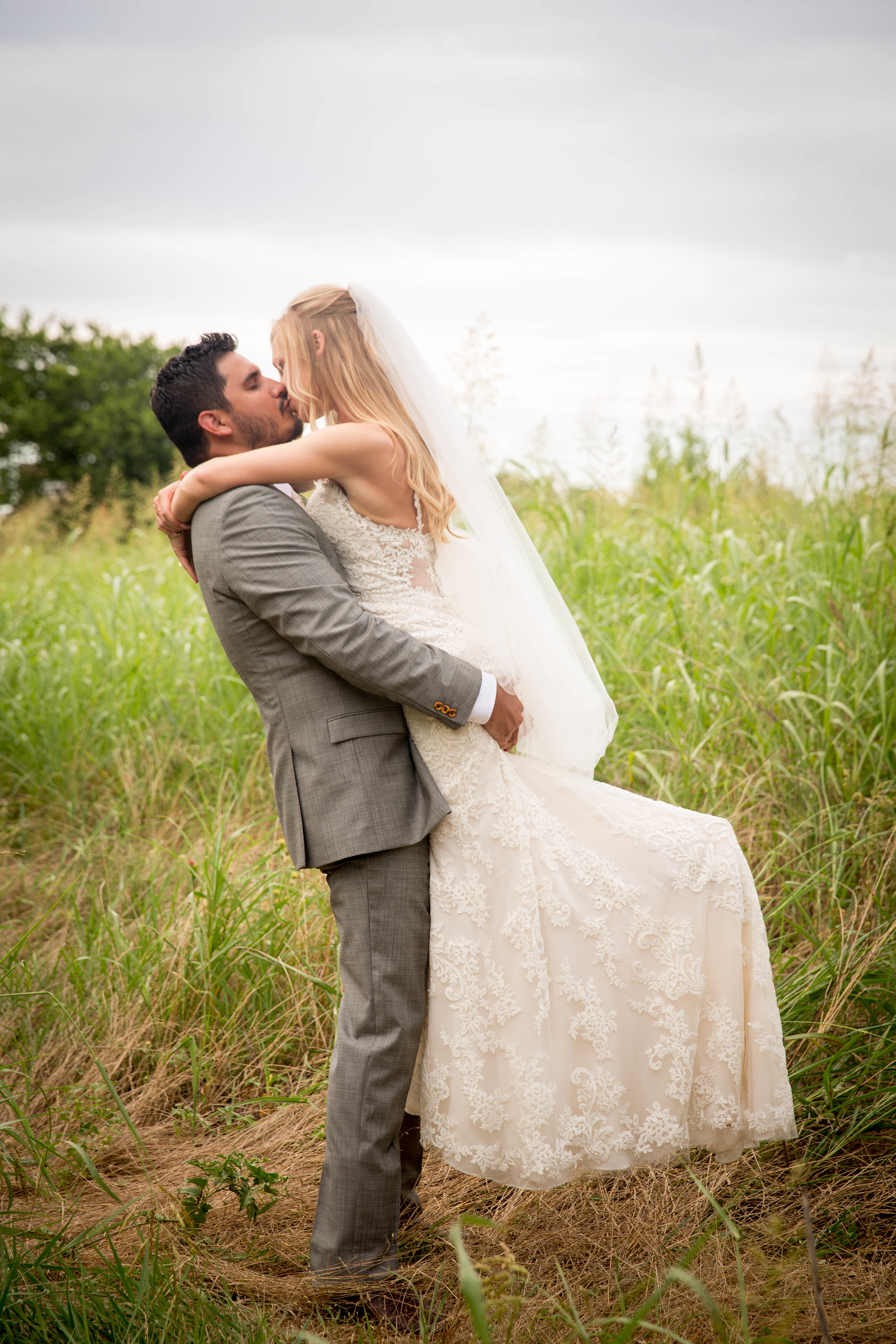 groom wearing a grey suit lifts his blonde bride in the air to kiss her in a field outside of their wedding venue