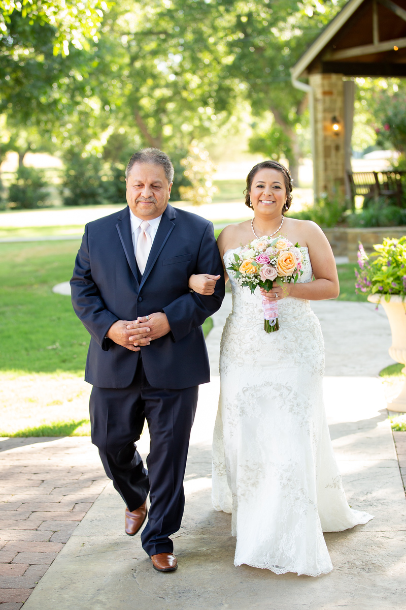 a bride being walked out of the wedding venue to the aisle by her father