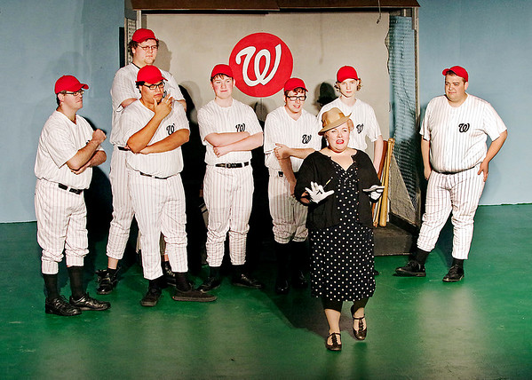 """Mark Maynard   for The Herald Bulletin<br /> As the Washington Senators look on, reporter Gloria Thorpe (Kirby Gilliam) tests-out some nicknames for their new star player, Joe Hardy, in """"Damn Yankees"""" presented by Anderson's Mainstage Theatre."""