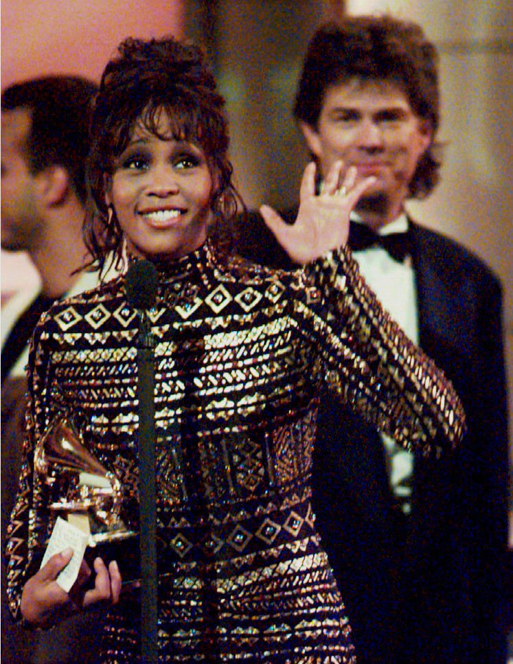 """. NEW YORK, UNITED STATES:  Whitney Houston waves to the crowd at the 36th Annual Grammy Awards in New York 01 March 1994 after she was honored for Record of the Year, \""""I\'ll Always Love You,\"""" and Album of the Year, the soundtrack from the film \""""The Bodyguard.\"""" At rear is her producer David Foster, who shared the honors with her. (POOL/AFP/Getty Images)"""