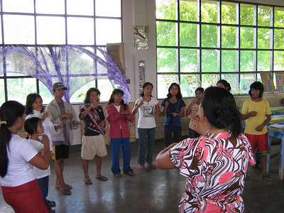 Lay Gospel Outreach Bible Worker, Sarah Famisaran, leads in signed singing - teaching signs while singing.  Some of the deaf students in this new school knew little formal signing when they started to attend this new school.