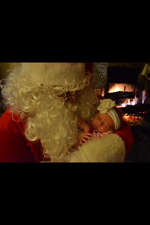 Granddaughter Kyndal Noble, daughter of Kyle and Kristen Noble, getting cozy with Santa.<br /> <br /> Photographer's Name: Jackie Michael<br /> Photographer's City and State: Anderson, Ind.