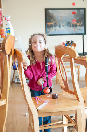 "Charlotte's second ""solution"" to the engineering challenge.  She first made a lever which flung the ball in (that worked).  Then she made this interesting contraption with a spoon hanging from dental floss.  She wanted to use the turkey baster to blow the spoon to hit the ball off of a platform."