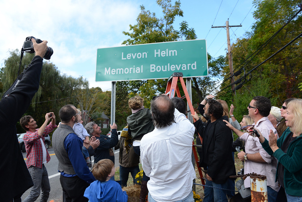 . Tania Barricklo-Daily Freeman  Amy Helm, on ladder, the daughter of Levon Helm, unveils a plaque that dedicated Rt 375 in Hurley to her late father at a cermony Friday afternoon.