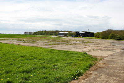 Standing on the threshold of runway 19 at RAF Desborough looking towards two of the hangars which are in industrial use.