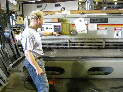Chuck Keskey with the large metal shearing press