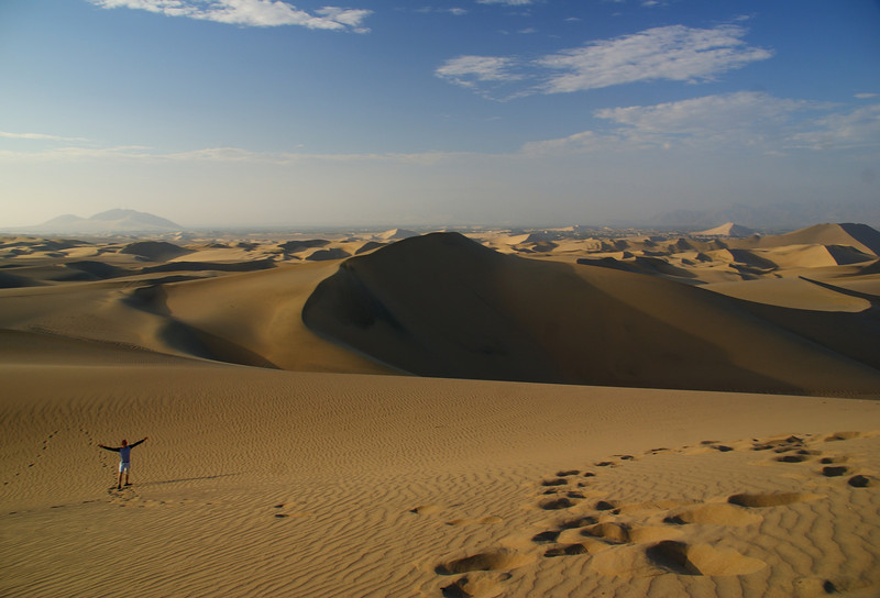 Nomadic Samuel experiencing the grand scale of the Huacachina oasis desert in Peru.