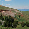Rocky outcrops with red soil break up hillsides with  the Centennial Mountains in the background.