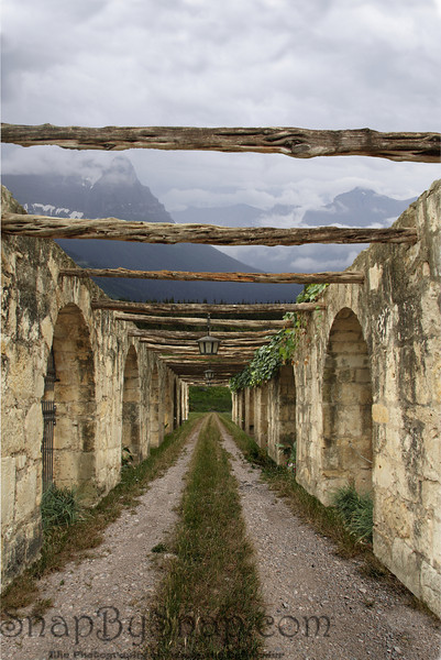 Pathway to the Mountains<br /> <br /> This is actually a combination of three images.  The ground is from the plains of Montana.  The background and sky is from Glacier National Park.  The walls and wood beams are from the Alamo in Texas.
