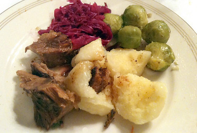 Schaeufele (pork roast), red cabbage, brussel sprouts, and Knoedel (dumpling, made from poached or boiled potatoes) served with gravy.