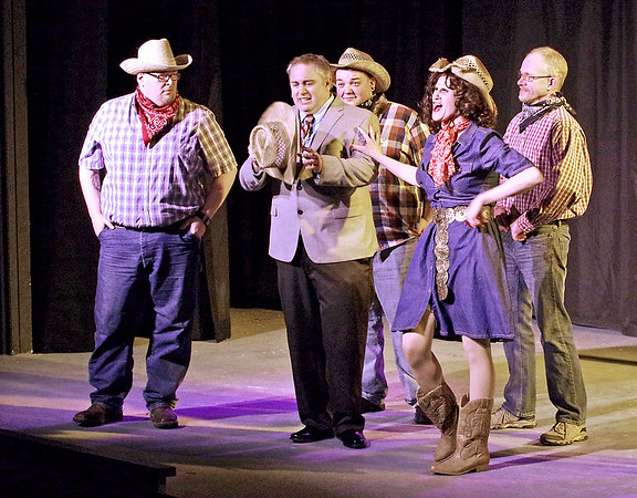 "Mark Maynard | for The Herald Bulletin<br /> As the ranch hands look on, Lawrence Jamerson (Eddie Franklin) is forced to don a straw cowboy hat by his supposed fiancee, rich Oklahoman Jolene Oaks (Jamie Conway), in ""Dirty Rotten Scoundrels"" at Anderson's Mainstage Theatre."