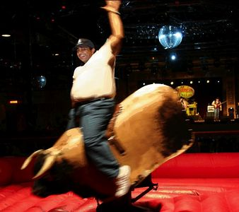 While I did ride this mechanical bull and the face is mine -- the body of the big guy riding the bull is not mine. Photo doctored by Perry Patrick. Perry's caption: The bull is Rajiv's only recourse to resolve his trips to Gilley's all-u-can-eat buffet