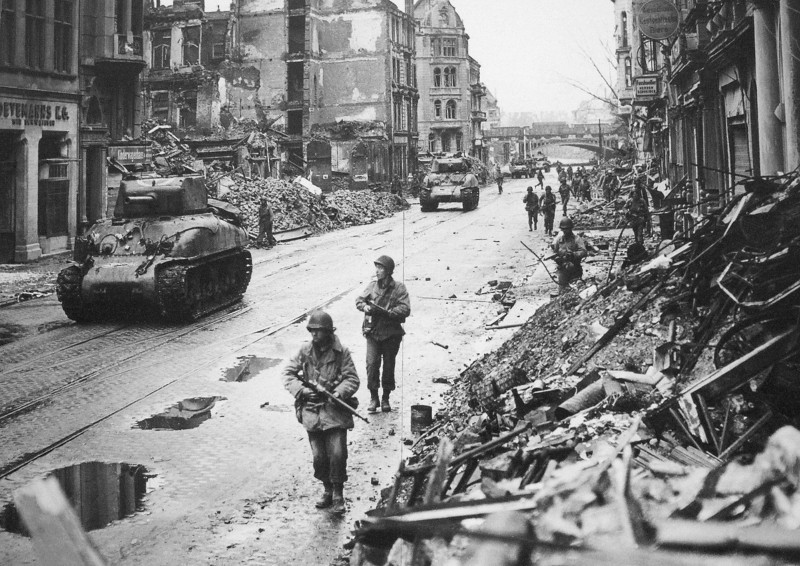 A photo of American infantry supporting Sherman Tanks in Northern France.
