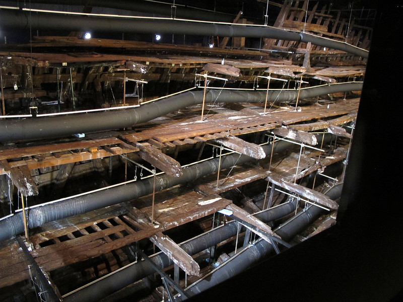 The remains of the hull, now fully impregnated with Ethylene Glycol preservative wax, being dried out for 2-3 years by dry air delivered by the huge rubber hoses.   On completion of the drying process the hoses will be removed.