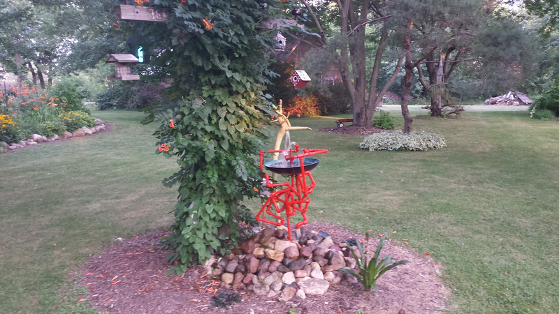 One of Doug's many creations on this amazing property; this piece blends with the orange lilies.