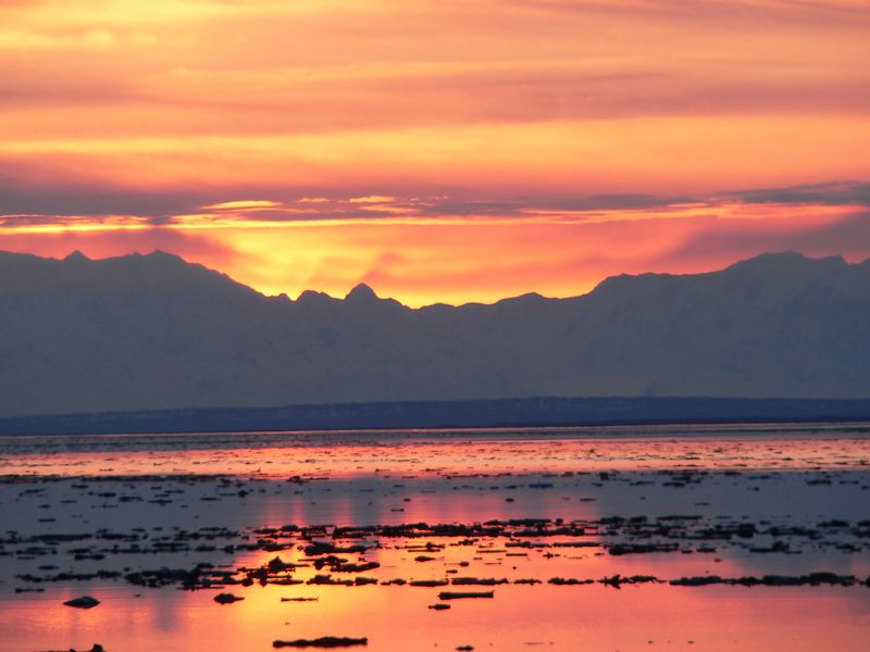 The sun sets behind the Alaska Range at  the mouth of Knik Arm.