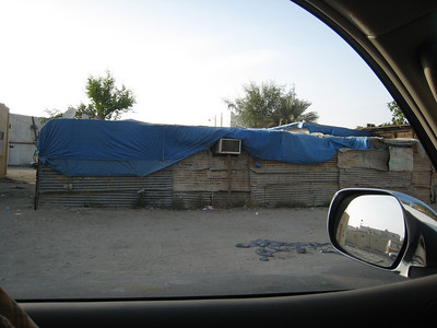 The other side of Dubai: A house in the backblocks of Satwa, made of corrogated iron with a plastic tarp roof, but it still has air-con!