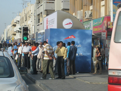 """The """"main drag"""" of Satwa.  A crowd of people waiting for the bus.  The flash, modern, air conditioned bus stops have been in use for only a couple of weeks but overnight this one, like all the others in Dubai, has been closed off and nobody seems to know why.  Summer fast approaches and passengers are having to stand out in the heat without any shelter at all."""