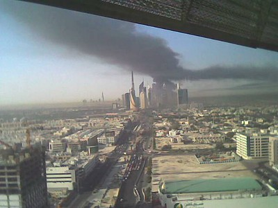 A huge explosion early this morning rocked the Al Quoz industrial area of Dubai sending a mushroom cloud of smoke high into the air. Typical Dubai, nobody knows exactly what has happened, some think an electricity substation has blown up, others that its fireworks factory. As the pall of black smoke is still growing over Dubai, *something* out there is still burning. One of my colleagues who lives close by the site of the explosion (near the National Taxi Station behind the old Grand Mall) says that when the explosion happened the windows rattled and her room shook so much that she thought a car or truck had hit the house. She said that shortly afterwards the Police and fire service were on the scene but that visibility on the roads in the area was minimal as the smoke was so thick. The explosions, and I'm told there was one large initial explosion followed by several smaller blasts, were felt in Jumeirah where windows rattled.  This photo was taken from BurJuman by my colleague Sean Korney just after the explosion happened.