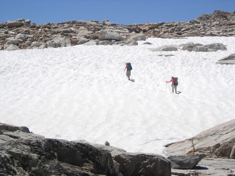 Some fellow hikers cross a snow field.