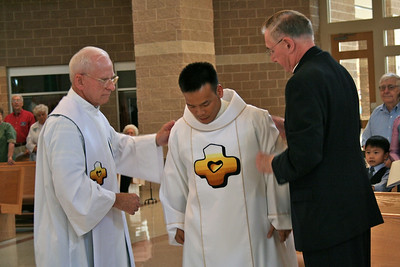 Fr. John Czyzynski and Br. Ben Humpfer help Dn. Duy with his vestments.