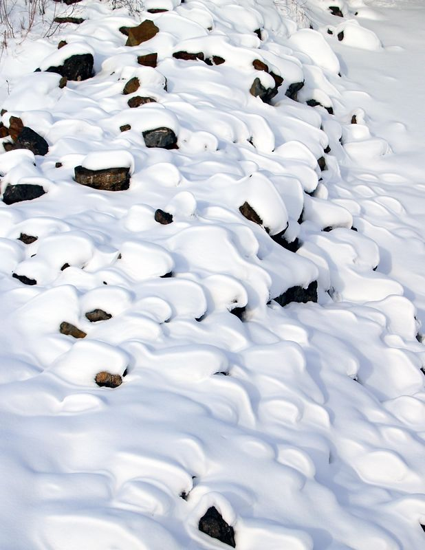 Snow covered rocks on the bank of the Knick River. Palmer, Alaska