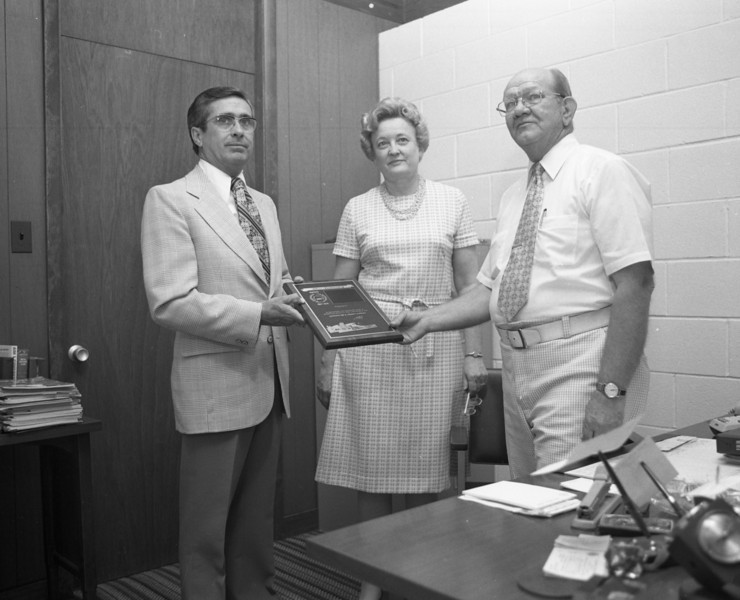 J.Lowell Marvin, Special Agent for Economy Fire & Casualty Company, presents a 25 Year Plaque to Millie C. and G. A. Shaffer of the G. A. Shaffer Agency of Troy, Illinois.