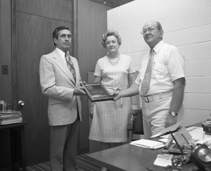 J. Lowell Marvin, Special Agent for Economy Fire & Casualty Company, presents 25 Year Plaque to Millie C. and G. A. Shaffer of the G. A. Shaffer Agency of Troy, Illinois.