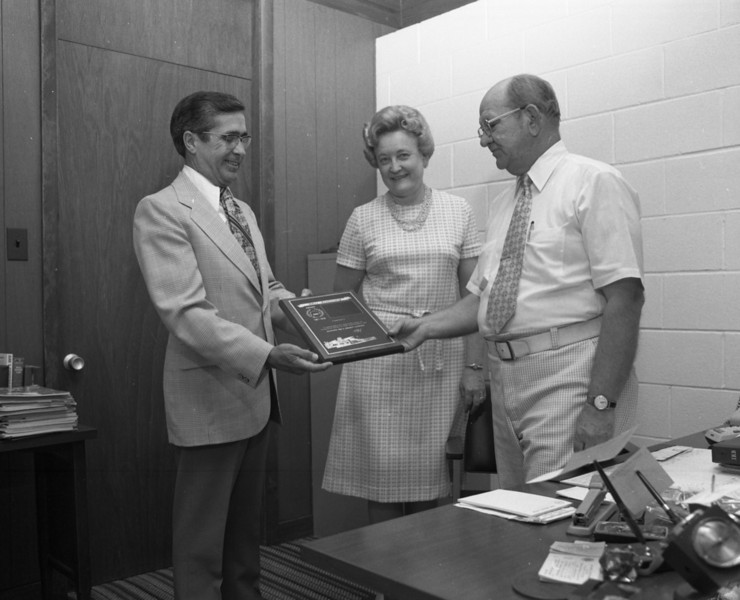 J. Lowell Marvin, Special Agent for Economy Fire & Casualty Company, presents a 25 Year Plaque to Millie C. & G. A. Shaffer of the G. A. Shaffer Agency of Troy, Illinois.